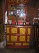 Credenza con decori simbolici tibetani su cui poggia teca con statua
